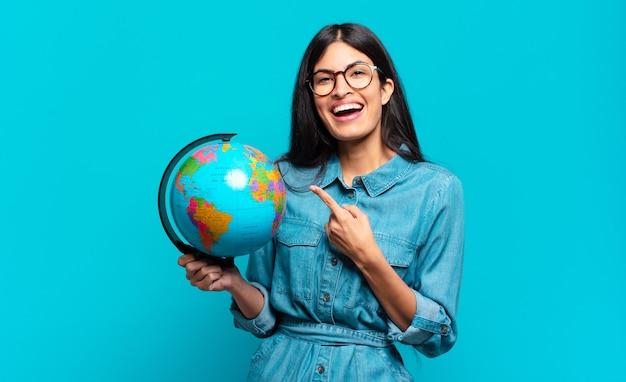 Młoda kobieta latynoska patrząc podekscytowana i zdziwiona, wskazując na bok i do góry, aby skopiować przestrzeń. koncepcja planety ziemi