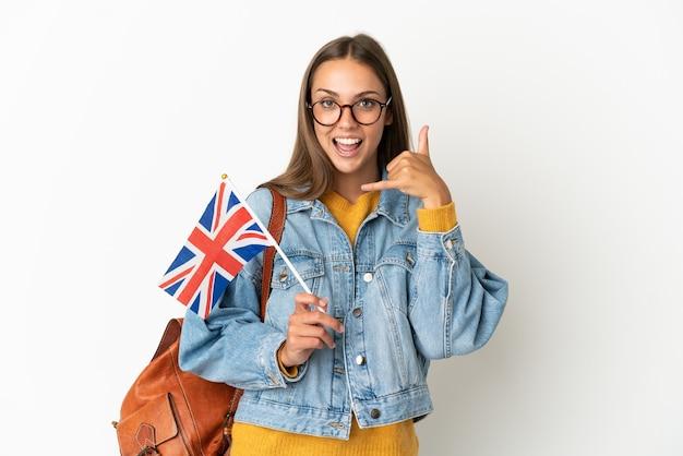 Młoda kobieta latynoska trzyma flagę wielkiej brytanii na na białym tle, co telefon gest. oddzwoń do mnie znak
