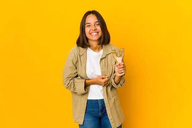 Młoda kobieta latynoska trzyma procę, śmiejąc się i bawiąc.