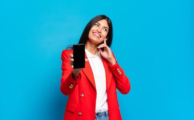 Młoda kobieta latynoska uśmiecha się szczęśliwie i marzy lub wątpi, patrząc w bok. miejsce na kopię ekranu telefonu