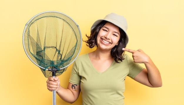 Młoda kobieta latynoska uśmiechając się pewnie wskazując na swój szeroki uśmiech. koncepcja sieci rybackiej