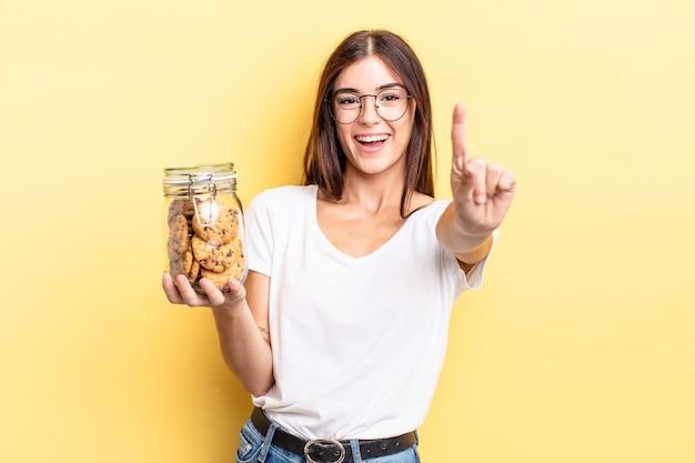 Młoda kobieta latynoska uśmiechnięta i patrząca przyjaźnie, pokazując numer jeden. koncepcja butelki ciasteczek
