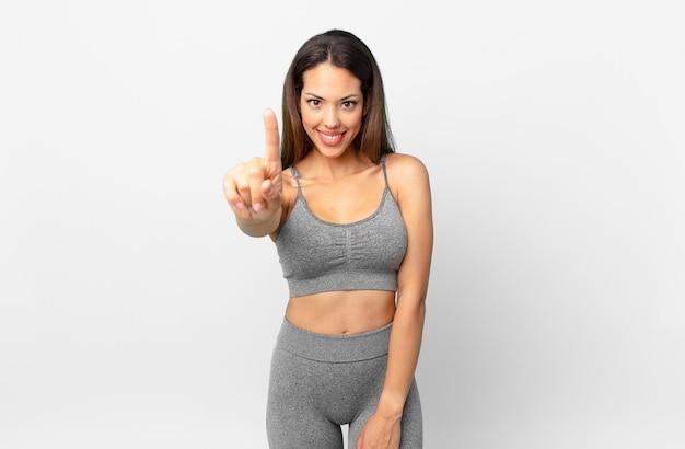 Młoda kobieta latynoska uśmiechnięta i patrząca przyjaźnie, pokazując numer jeden. koncepcja fitness