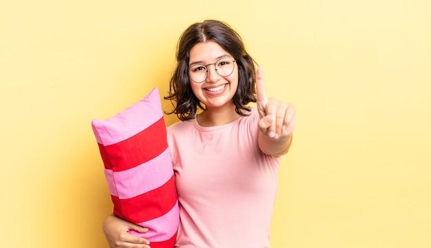 Młoda kobieta latynoska uśmiechnięta i patrząca przyjaźnie, pokazując numer jeden. koncepcja porannego przebudzenia