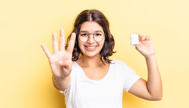Młoda kobieta latynoska uśmiechnięta i patrząca przyjaźnie, pokazująca numer cztery. koncepcja pigułek na chorobę