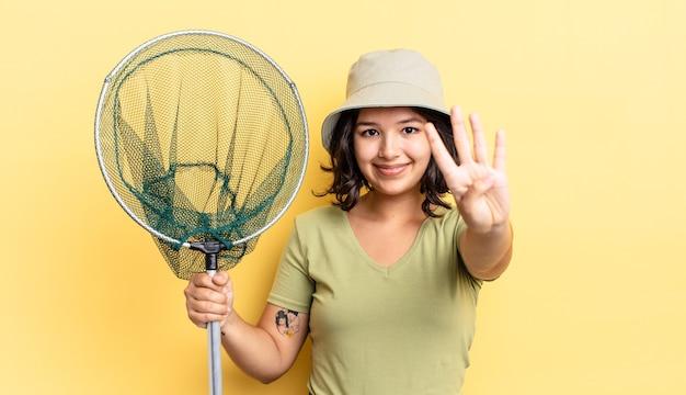 Młoda kobieta latynoska uśmiechnięta i patrząca przyjaźnie, pokazująca numer cztery. koncepcja sieci rybackiej