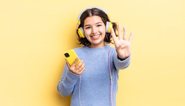Młoda kobieta latynoska uśmiechnięta i patrząca przyjaźnie, pokazująca numer cztery. koncepcja słuchawek i smartfona