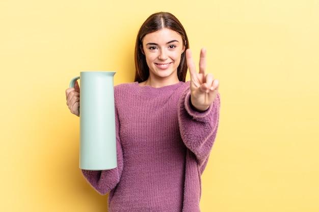Młoda kobieta, latynoska, uśmiechnięta i przyjazna, pokazując numer dwa. koncepcja termosu do kawy