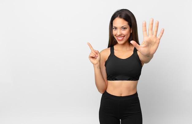 Młoda kobieta latynoska uśmiechnięta i przyjazna, pokazująca numer pięć. koncepcja fitness