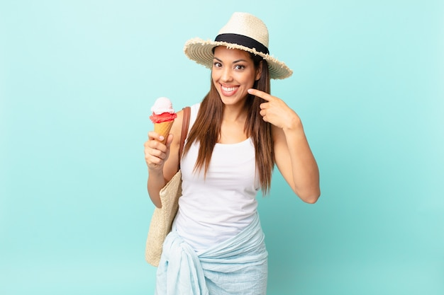 Młoda kobieta latynoska uśmiechnięta pewnie wskazując na swój szeroki uśmiech i trzymająca lody. koncepcja suma
