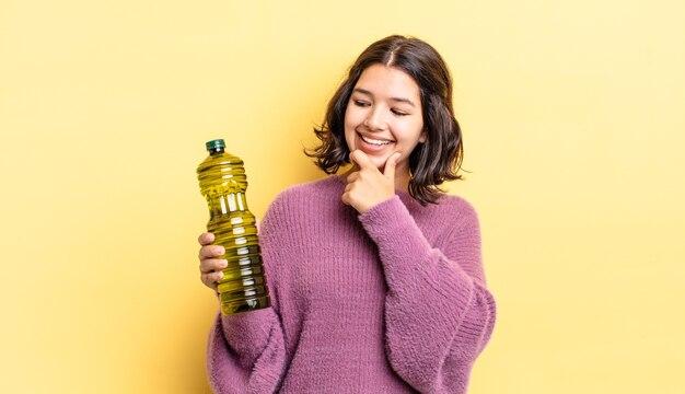 Młoda kobieta latynoska uśmiechnięta ze szczęśliwym, pewnym siebie wyrazem twarzy z ręką na brodzie. koncepcja oliwy z oliwek