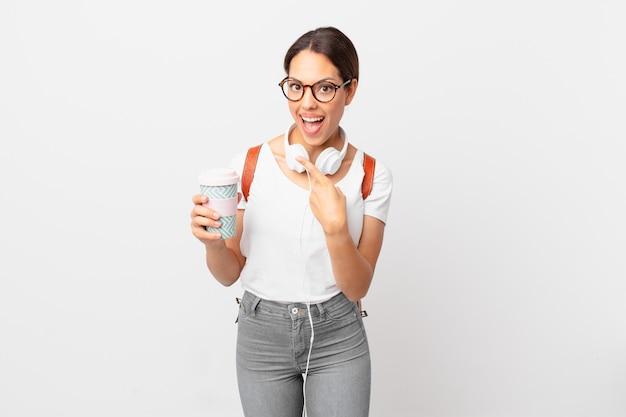 Młoda kobieta latynoska wygląda na podekscytowaną i zdziwioną, wskazując na bok. koncepcja studenta