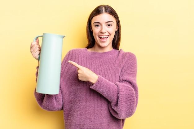 Młoda kobieta latynoska wygląda na podekscytowaną i zdziwioną, wskazując na bok. koncepcja termosu do kawy