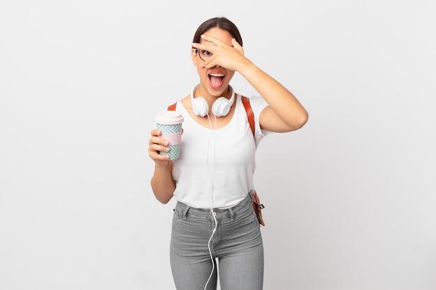 Młoda kobieta latynoska wyglądająca na zszokowaną, przestraszoną lub przerażoną, zakrywając twarz dłonią. koncepcja studenta