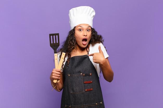 Młoda kobieta, latynoska, zszokowana i zaskoczona, z szeroko otwartymi ustami, wskazując na siebie. koncepcja szefa kuchni z grilla
