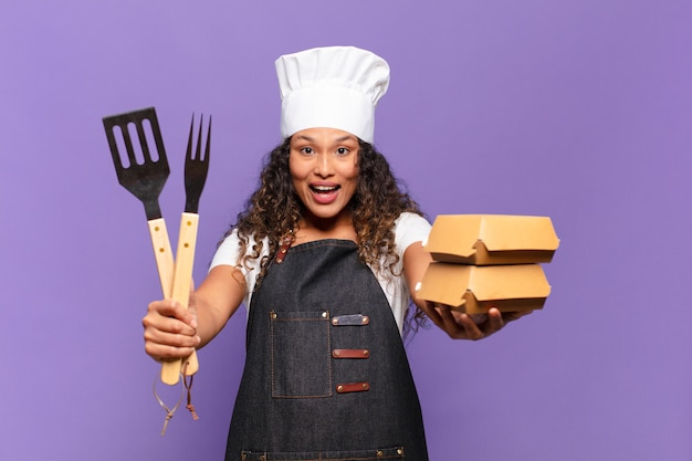 Młoda kobieta latynoska. zszokowana lub zdziwiona koncepcja szefa kuchni z grilla exssion