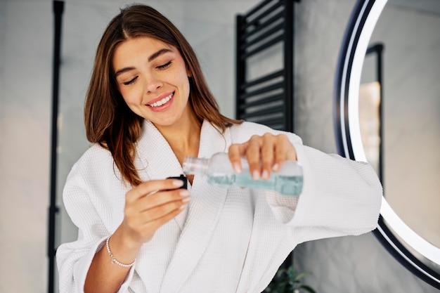 Młoda kobieta leje do mycia ust