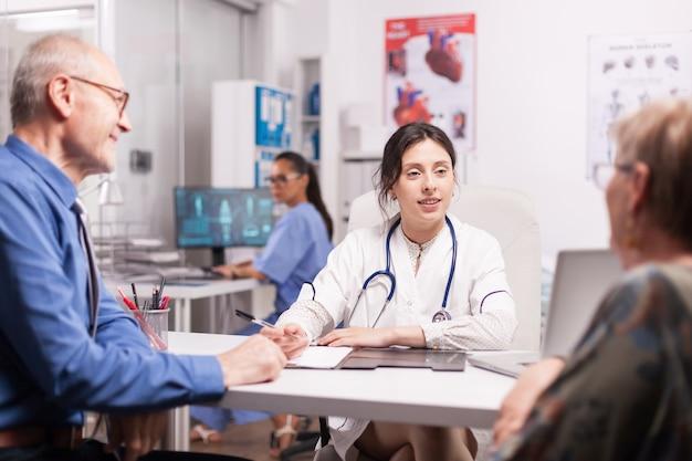Młoda kobieta lekarz bada staruszkowie w biurze szpitala na sobie biały fartuch i stetoskop. para emerytów na badanie lekarskie i pielęgniarka pracująca na komputerze.