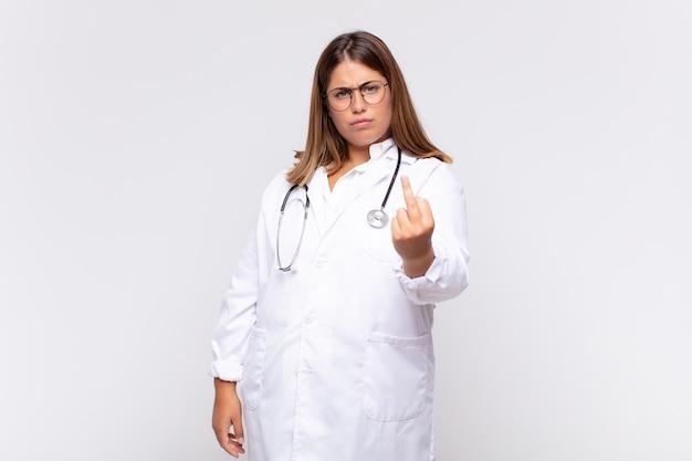 Młoda kobieta lekarz czuje się zła, zirytowana, zbuntowana i agresywna, macha środkowym palcem, walczy
