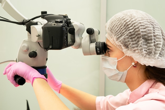 Młoda kobieta lekarz dentysta patrzy przez profesjonalny mikroskop w klinice dentystycznej