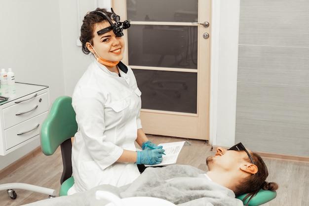 Młoda kobieta lekarz dentysta w miejscu pracy prowadzi badanie pacjenta. historia biorąc. sprzęt do pracy w miejscu pracy dla lekarza. stomatologia