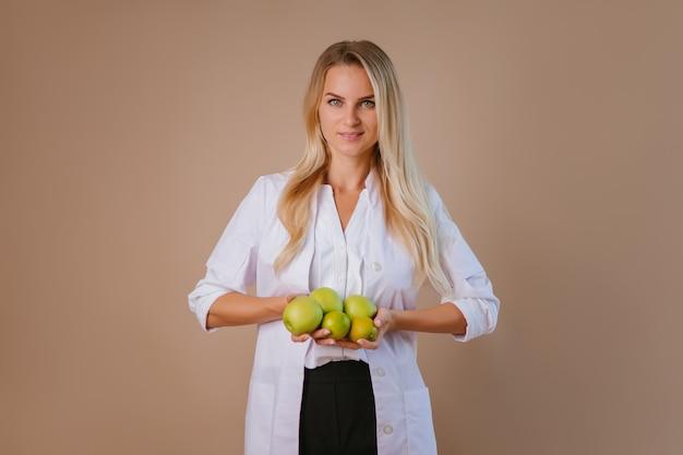 Młoda kobieta lekarz dietetyk uśmiecha się, trzymając zielone jabłka.
