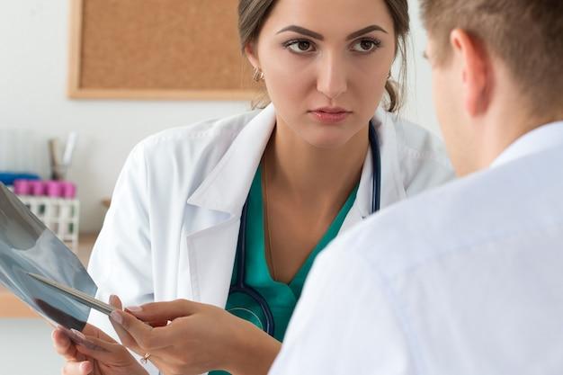 Młoda kobieta lekarz i jej kolega omawiający obraz rentgenowski