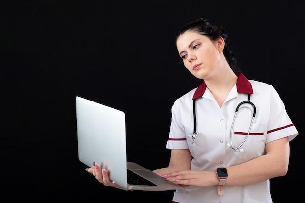 Młoda kobieta lekarz lub pielęgniarka trzymająca laptopa na białym tle na ciemnym tle, kopia przestrzeń