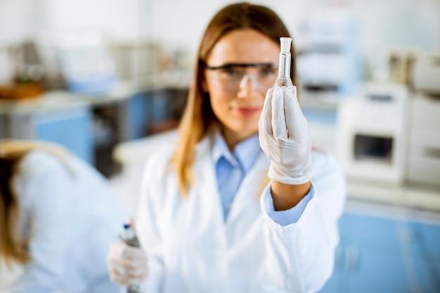 Młoda kobieta lekarz ma na sobie ochronną maskę na twarz w laboratorium trzyma kolbę z płynną próbką