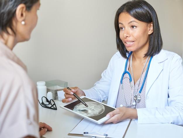 Młoda kobieta lekarz medycyny mieszanej w białym mundurze medycznym omawia wyniki mri z pacjentką w średnim wieku, trzymającą obrazowanie rezonansem magnetycznym mózgu i wyjaśniającą diagnozę medyczną klientowi