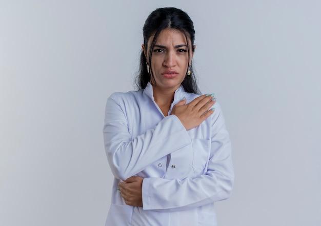 Młoda kobieta lekarz noszenie szaty medycznej patrząc kładąc rękę na barku cierpiących na ból na białym tle
