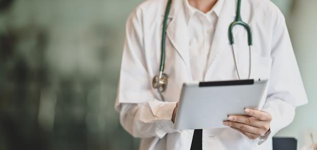 Młoda kobieta lekarz podsumowuje wykresy pacjenta z cyfrowego tabletu