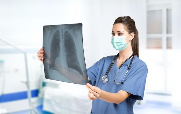 Młoda kobieta lekarz posiadający koncepcję radiografii płuc, koronawirusa i choroby płuc