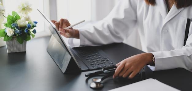 Młoda kobieta lekarz pracuje na wykresach medycznych i dokument w swoim biurze