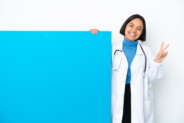 Młoda kobieta lekarz rasy mieszanej z dużą tabliczką na białym tle uśmiechnięta i pokazująca znak zwycięstwa