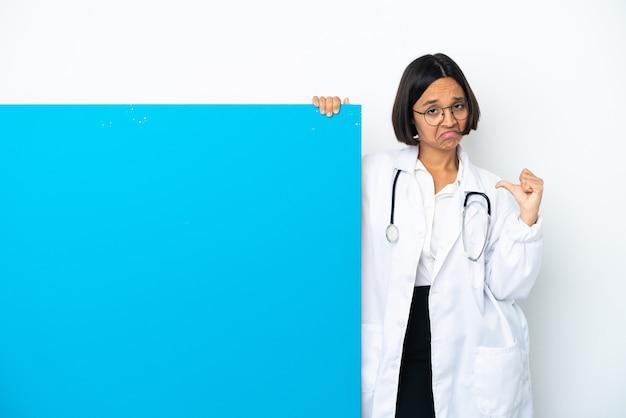 Młoda kobieta lekarz rasy mieszanej z dużym afiszem na białym tle dumna i zadowolona z siebie