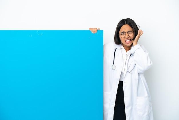 Młoda kobieta lekarz rasy mieszanej z dużym afiszem na białym tle sfrustrowana i zakrywająca uszy