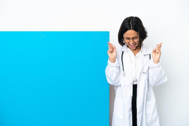 Młoda kobieta lekarz rasy mieszanej z dużym afiszem na białym tle ze skrzyżowanymi palcami