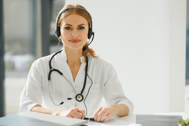 Młoda kobieta lekarz rozmawia z pacjentem online z gabinetu lekarskiego. klient konsultingowy lekarza na laptopie do czatu wideo w szpitalu