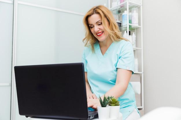Młoda kobieta lekarz rozmawia z pacjentem online z gabinetu lekarskiego