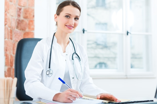 Młoda kobieta lekarz siedzi przy biurku przed oknem w klinice, pisząc plik lub dossier