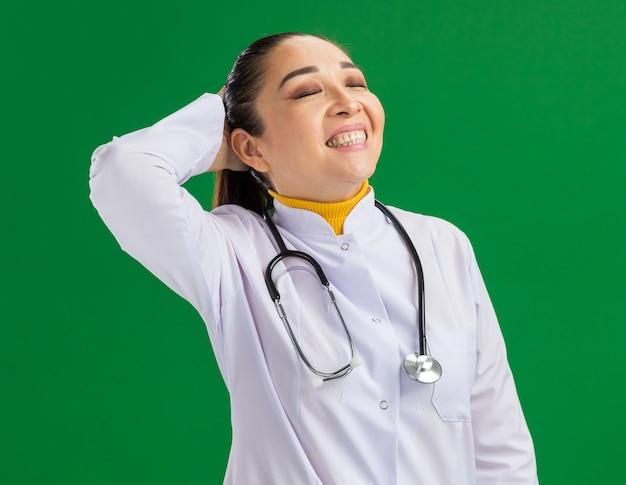 Młoda kobieta lekarz szczęśliwa i pozytywnie uśmiechnięta szeroko