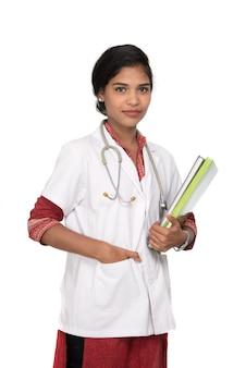 Młoda kobieta lekarz trzymając książkę ze stetoskopem
