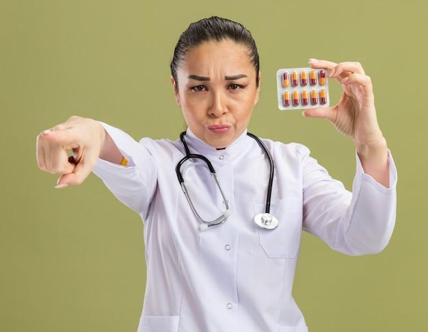 Młoda kobieta lekarz trzymająca blister z tabletkami wskazującymi palcem wskazującym na aparat patrząc z poważną miną