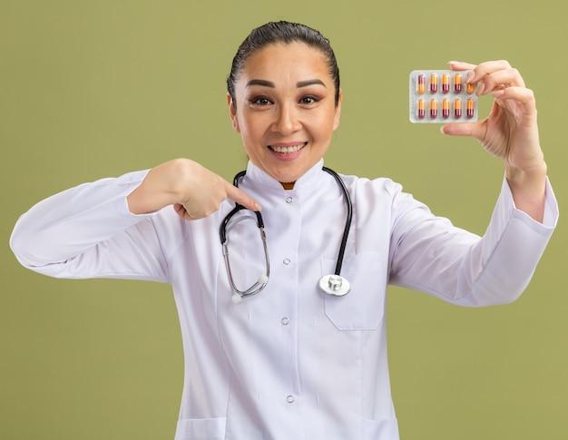 Młoda kobieta lekarz trzymająca blister z tabletkami wskazującymi palcem wskazującym, uśmiechając się pewnie