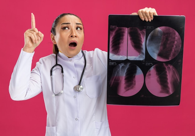 Młoda kobieta lekarz trzymająca prześwietlenie płuc patrząca w górę zdziwiona pokazująca palec wskazujący mający nowy pomysł