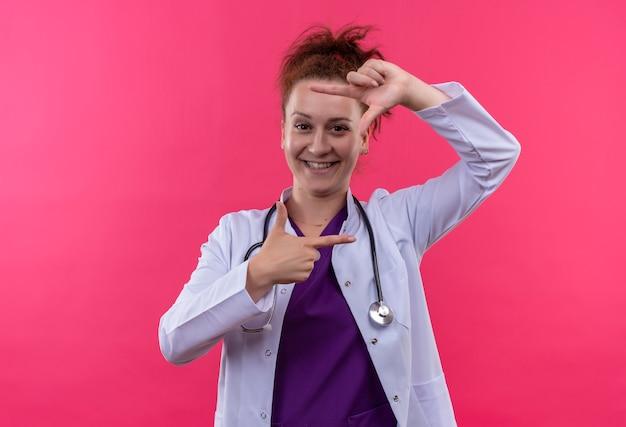 Młoda kobieta lekarz ubrana w biały fartuch ze stetoskopem, dzięki czemu ramka z palcami uśmiecha się radośnie patrząc przez tę ramkę stojącą nad różową ścianą