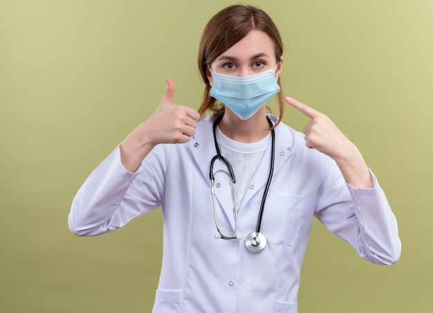 Młoda kobieta lekarz ubrana w szlafrok medyczny, maskę i stetoskop pokazujący kciuk do góry i wskazujący na jej maskę na odosobnionej zielonej ścianie