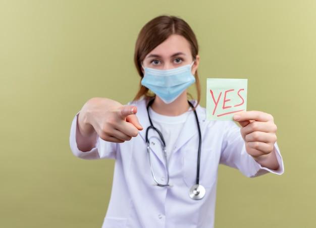 Młoda kobieta lekarz ubrana w szlafrok medyczny, maskę i stetoskop rozciągający tak notatkę i wskazujący na izolowaną zieloną ścianę