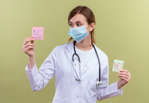 Młoda kobieta lekarz ubrana w szlafrok medyczny, maskę i stetoskop, trzymając tak i nie notatki i patrząc na żadną notatkę na odosobnionej zielonej ścianie